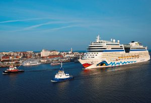 Schlepper ziehen die Aida in den Hafen